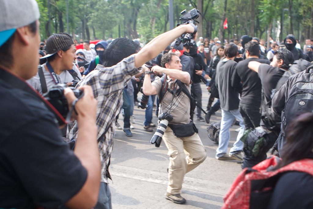 El fotógrafo Marco Ugarte intenta cubrirse al ser atacado por un grupo de manifestantes.,